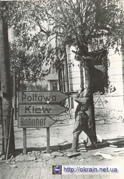 Советский солдат сбивает немецкие указатели в Кременчуге - фото 363